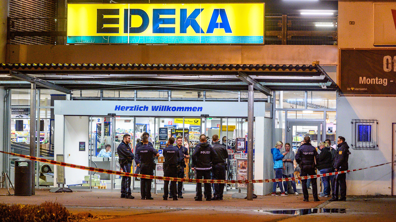 Einsatzkräfte stehen vor einem Supermarkt in Abensberg, vor dem Schüsse gefallen sind