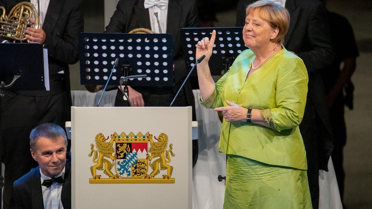 Rainer Riedl (u.l.), Pressesprecher des Bayerischen Ministerpräsidenten und der Staatsregierung, stellt der Bundeskanzlerin Angela Merkel (CDU) beim Staatsempfang anlässlich der Richard-Wagner-Festspiele in Bayreuth etwas am Rednerpult ein.