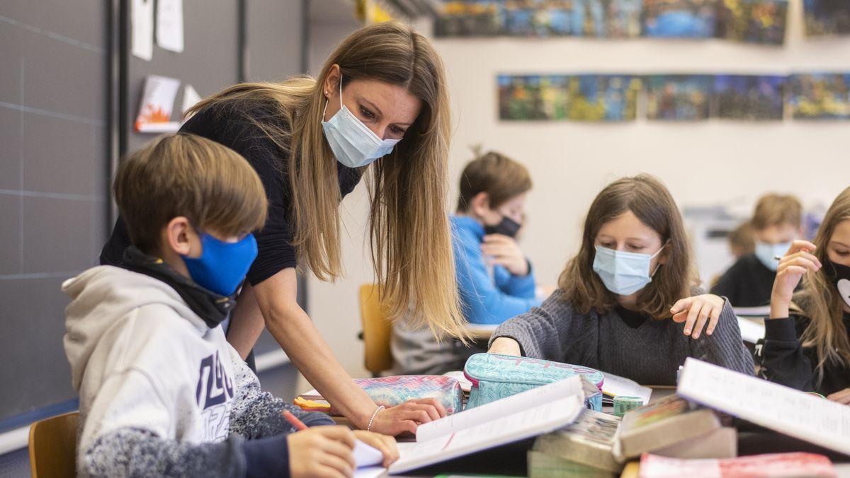 Lehrerin mit Kindern mit Atemschutzmasken im Unterricht