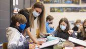 Lehrerin mit Kindern mit Atemschutzmasken im Unterricht   Bild:pa/KEYSTONE/Ennio Leanza