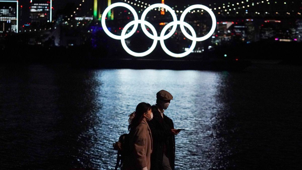 Tokio: Ein Mann und eine Frau gehen in der Nähe der über dem Wasser leuchtenden Olympischen Ringe auf der Insel Odaiba vorbei.