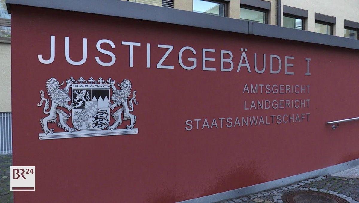 """Eingang zum Landgericht Coburg, daneben eine Mauer, auf der """"Justizgebäude"""" auf rotem Untergrund zu lesen ist."""