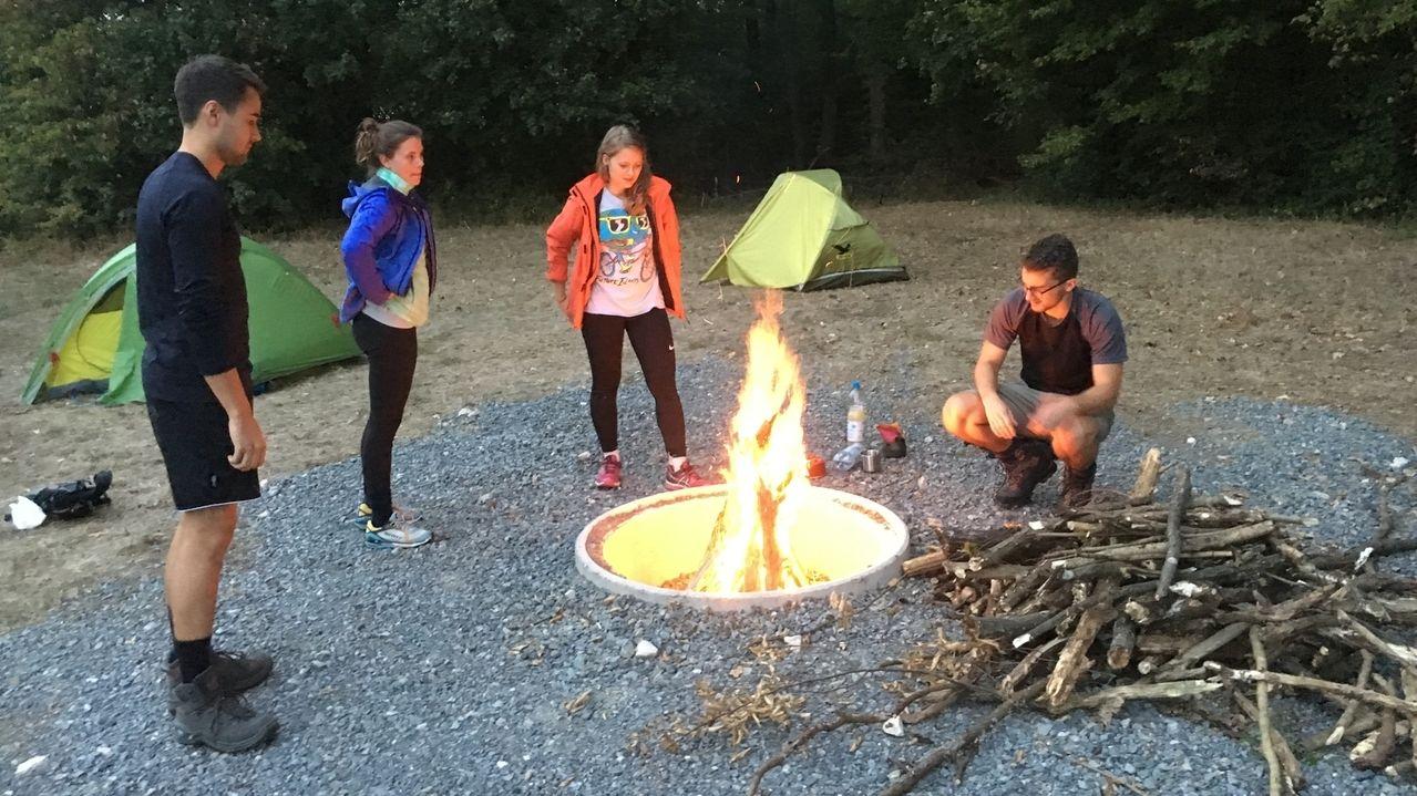 Wanderer stehen oder sitzen an einem Trekkingplatz im Steigerwald um ein Lagerfeuer herum.