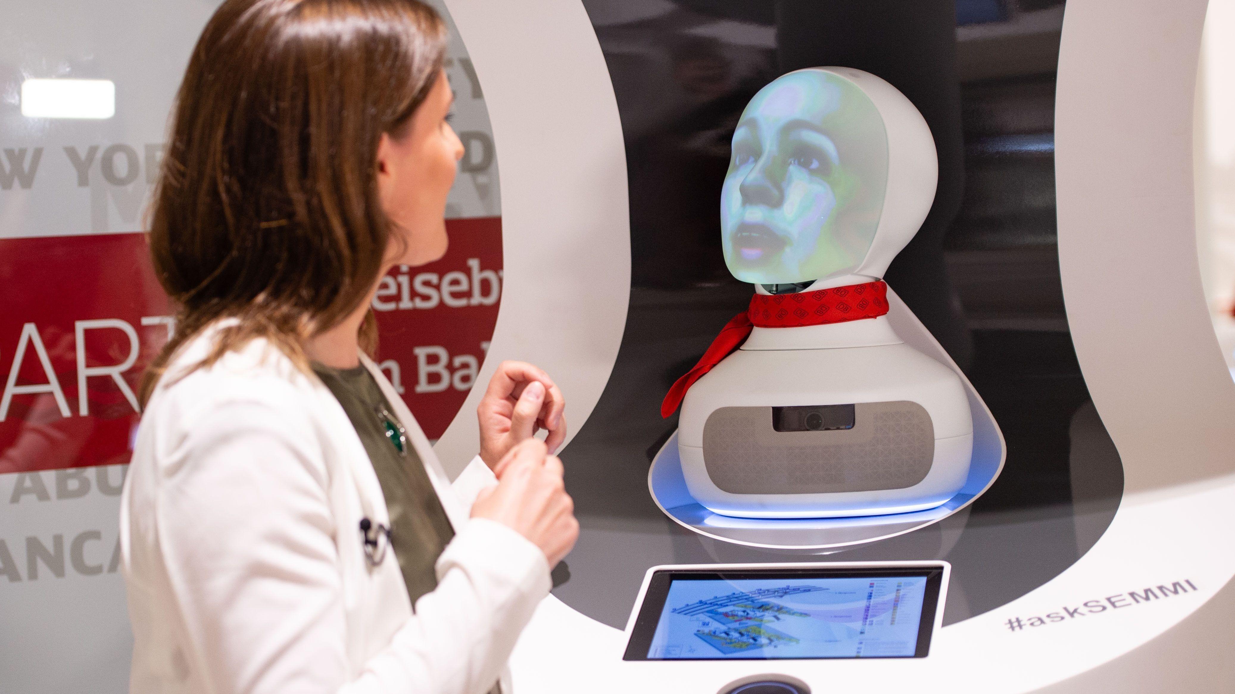 """Eine Frau spricht mit """"Semmi"""", einem Roboter vom Kundenservice der Deutsche Bahn, der auf Basis Künstlicher Intelligenz (KI) funktioniert."""