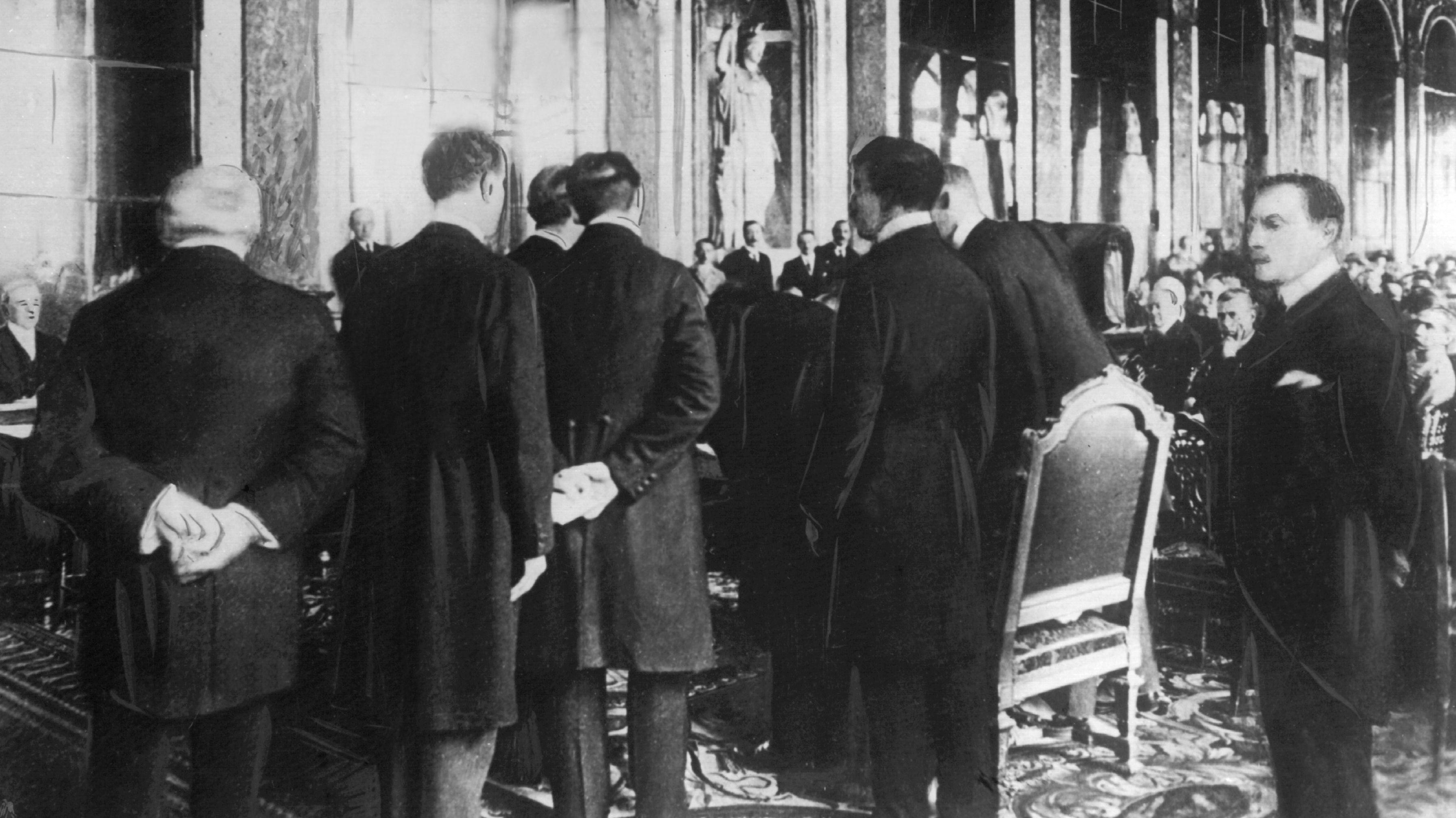 Ein historischer Augenblick: Der deutsche Außenminister Hermann Müller (M) unterschreibt den Versailler Friedensvertrag. Hinter ihm Johannes Bell. Historische Aufnahme vom 28. Juni 1919.