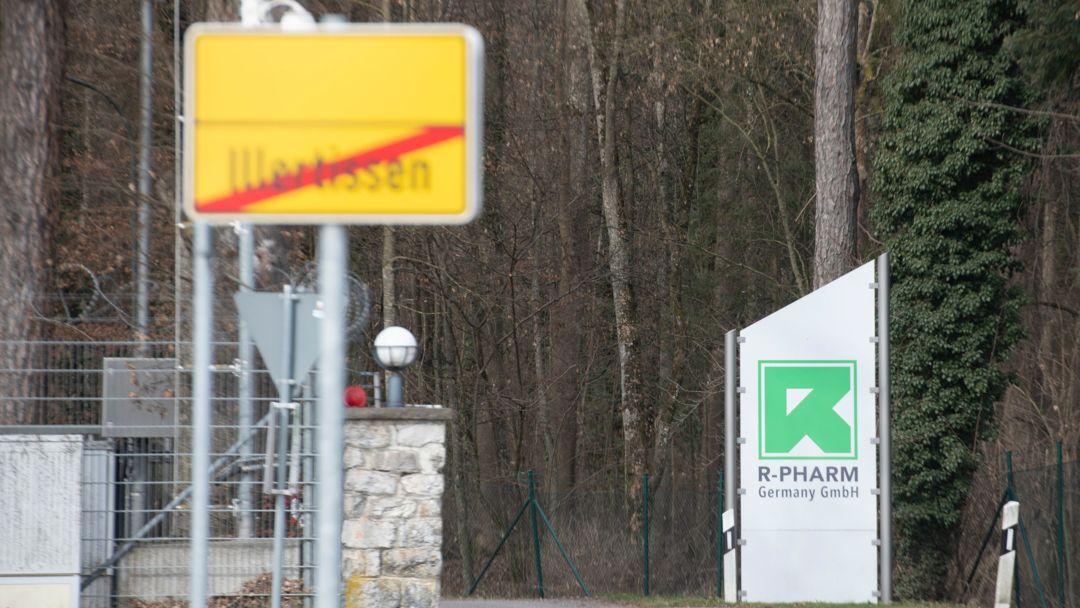 Ortsschild von Illertissen im Vordergrund, Zaun und Firmen-Logo der R-Pharm Germany GmbH im Hintergrund