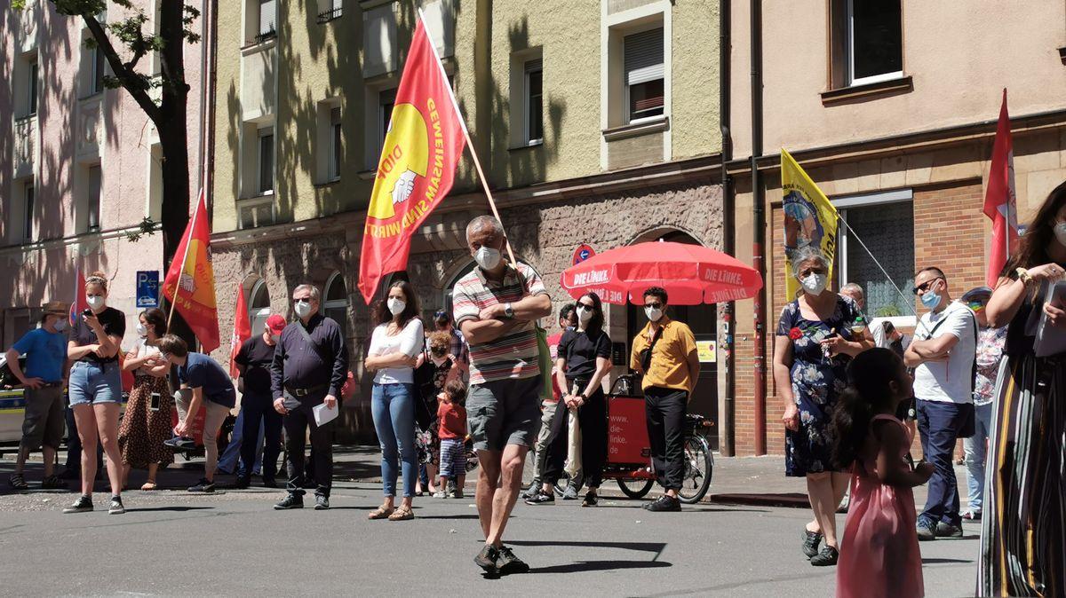 Menschen stehen auf der Straße, manche schwenken Fahnen