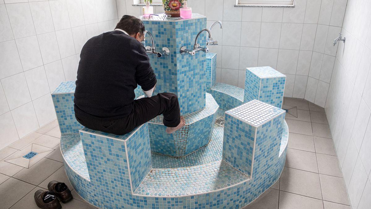 Ein Gläubiger sitzt zur rituellen Waschung am Brunnen in einer Moschee in Niedersachsen.