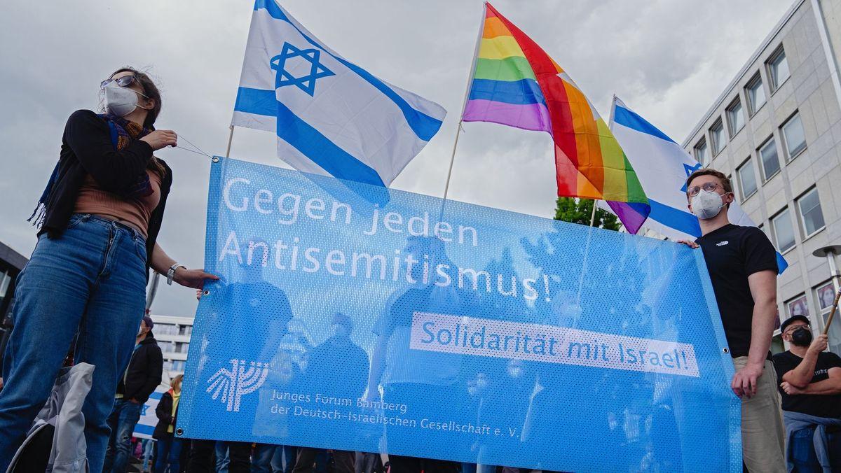 """Aktive des Jungen Forums Bamberg halten ein Transparent mit der Aufschrift """"Gegen jeden Antisemitismus"""" in die Höhe"""