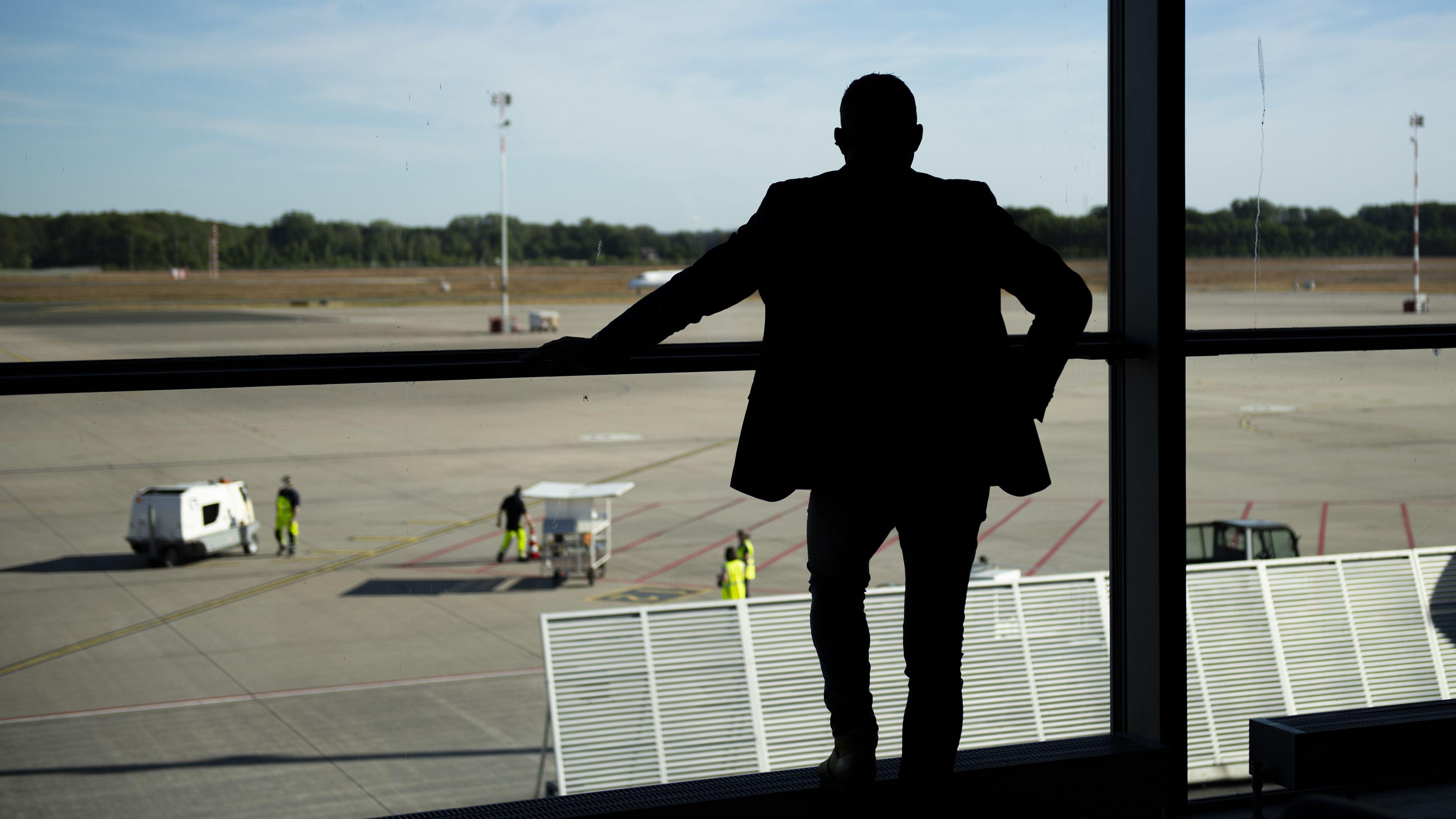 Ein Mann blickt auf ein leeres Rollfeld (Symbolbild)