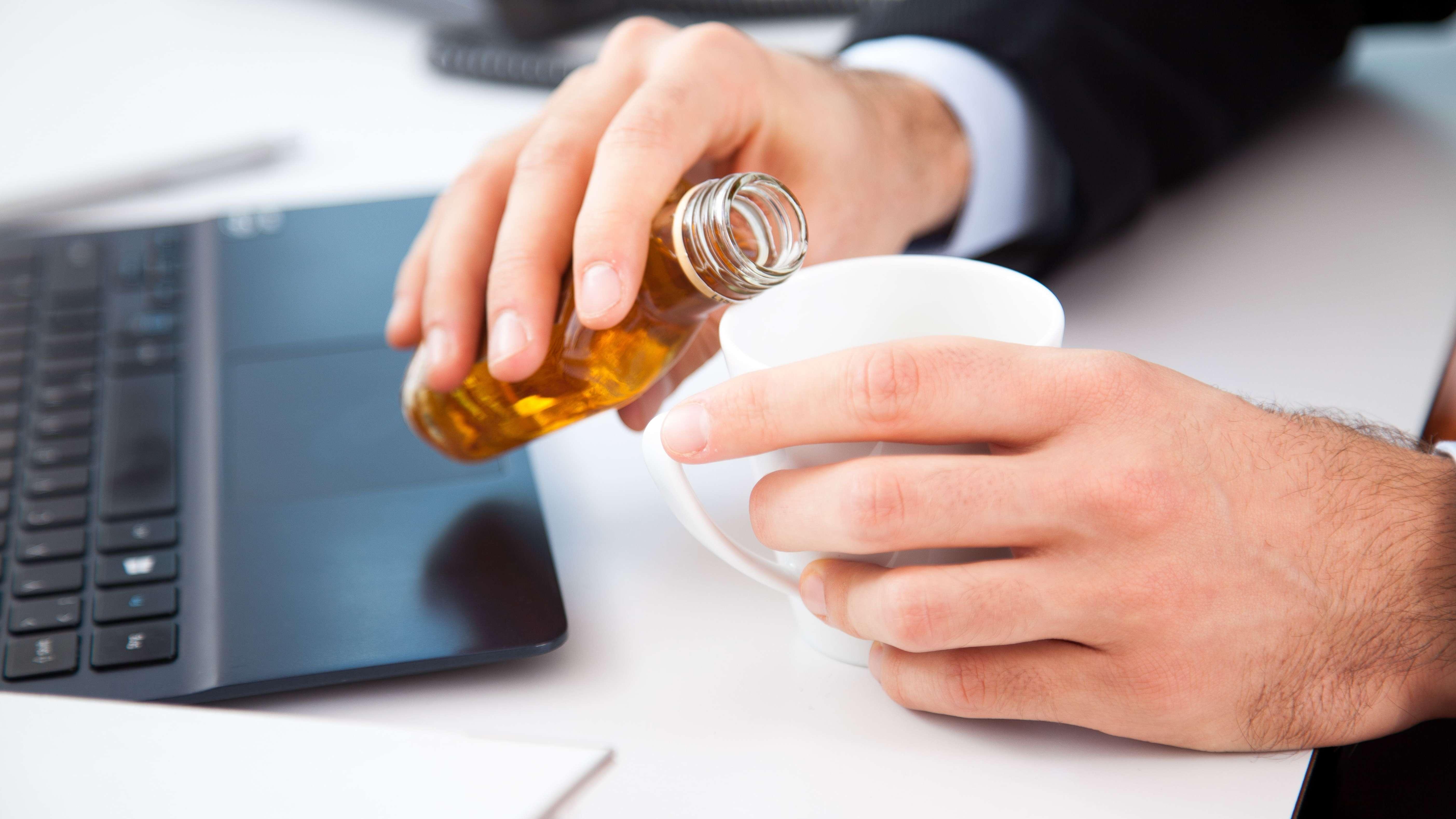 Ein junger Mann mischt am Arbeitsplatz Alkohol in seinen Kaffee
