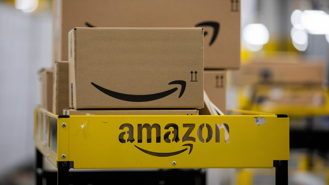Pakete liegen in einem Logistikzentrum des Versandhändlers Amazon auf einem Wagen.