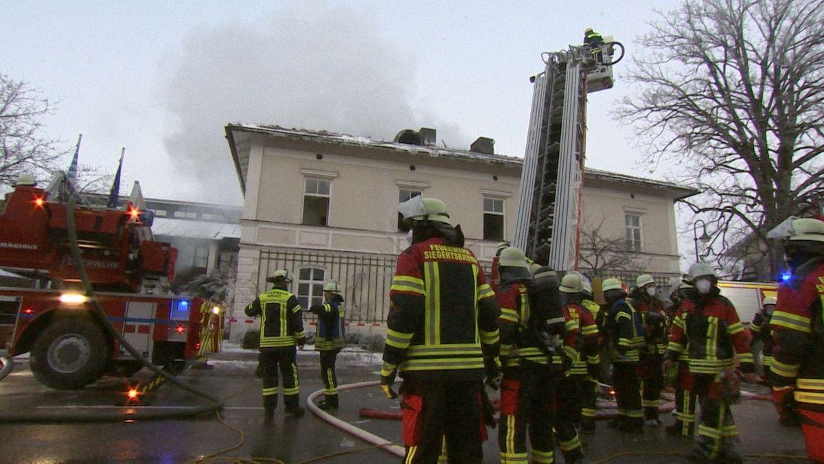 Feuerwehrwehr vor dem alten Rathaus. Aus dem Haus steigt Rauch auf.