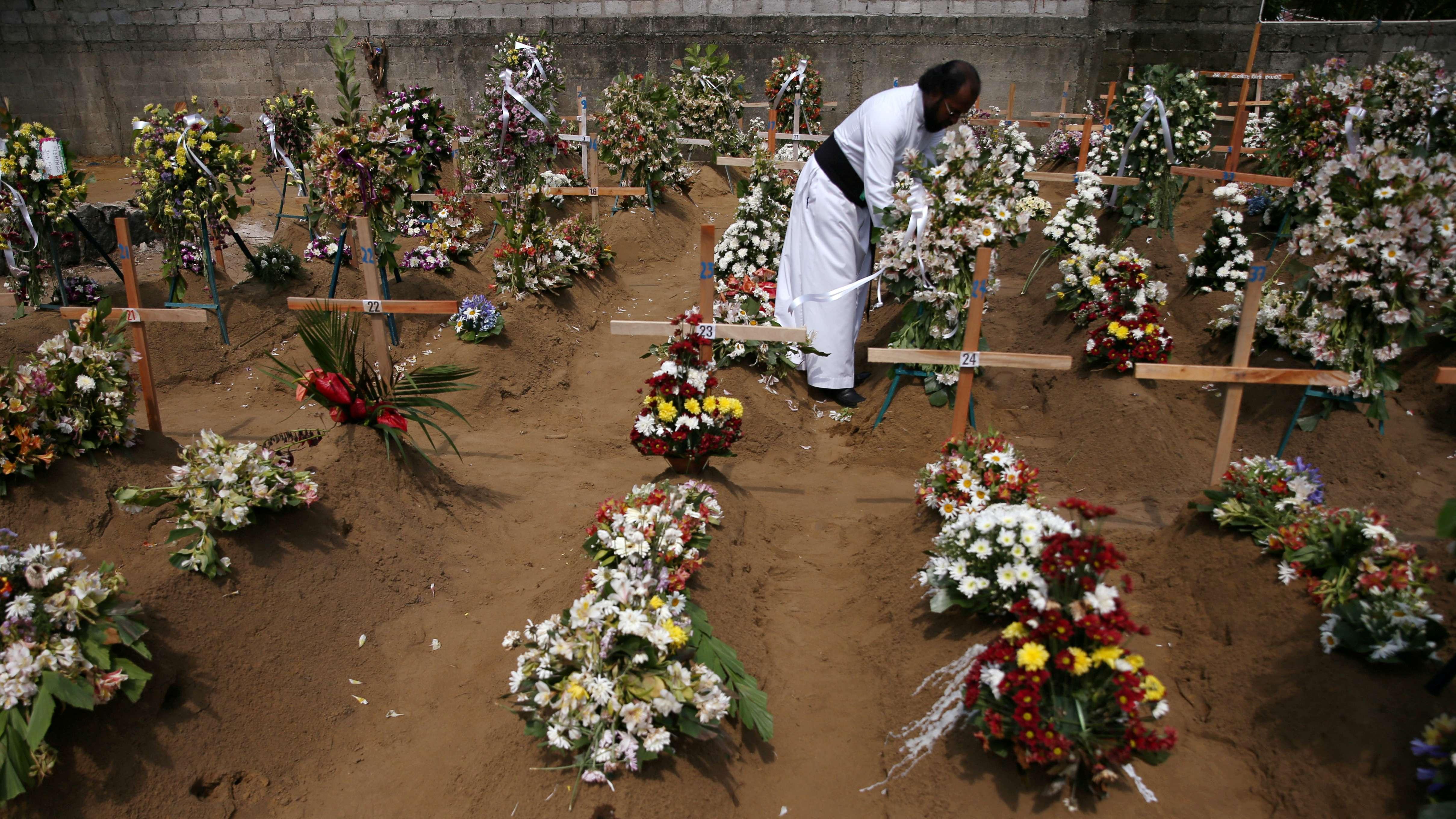 Ein Priester pflegt Gräber nach einer Messenbeerdigung von Anschlagsopfern in Negombo