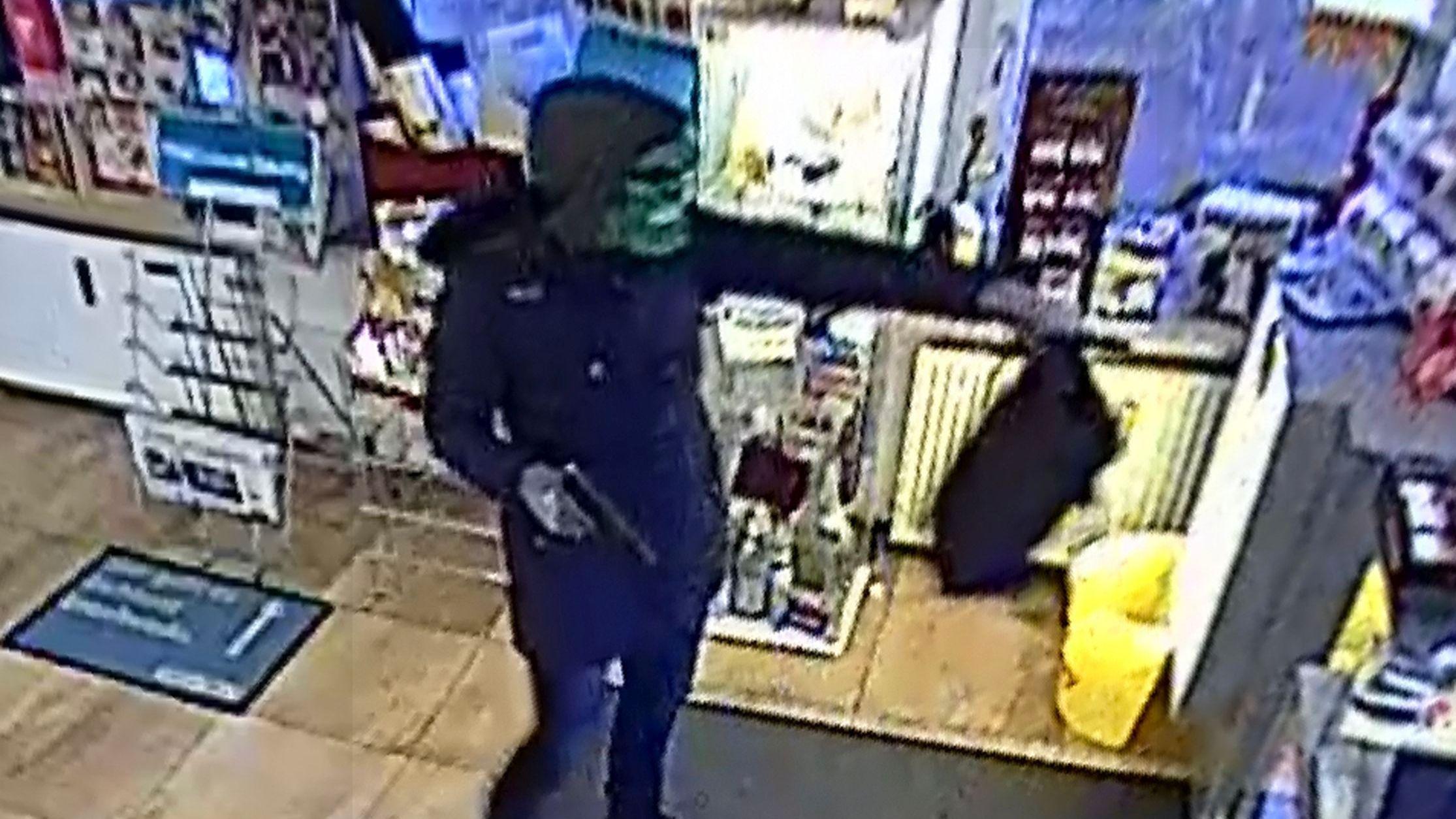 Ein Mann trägt eine blaue Jacke und eine grüne Maske und überfällt einen Laden