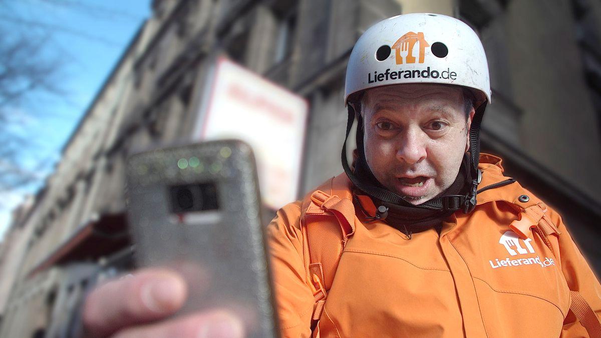 Lieferando-Fahrer schaut auf sein Handy.