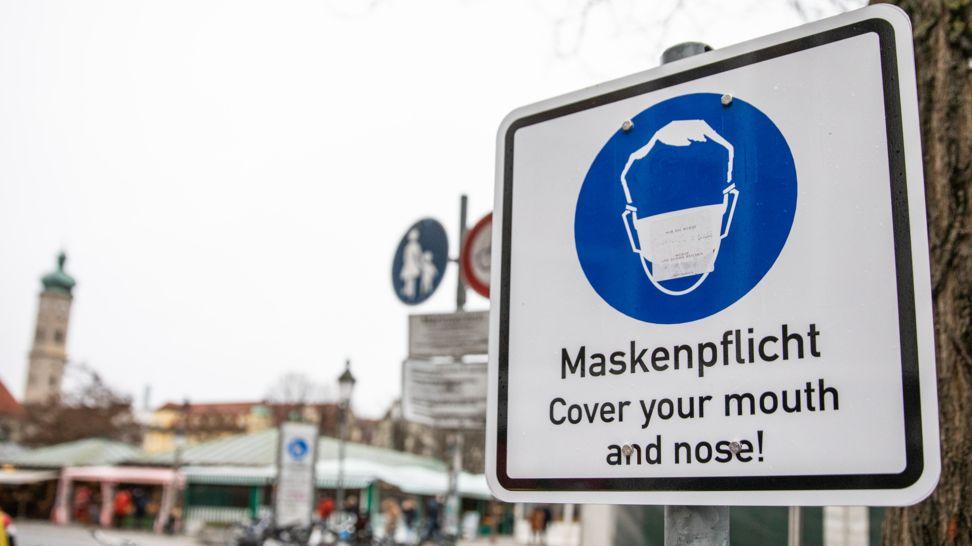 Schild weist am Viktualienmarkt in München auf Maskenpflicht hin.