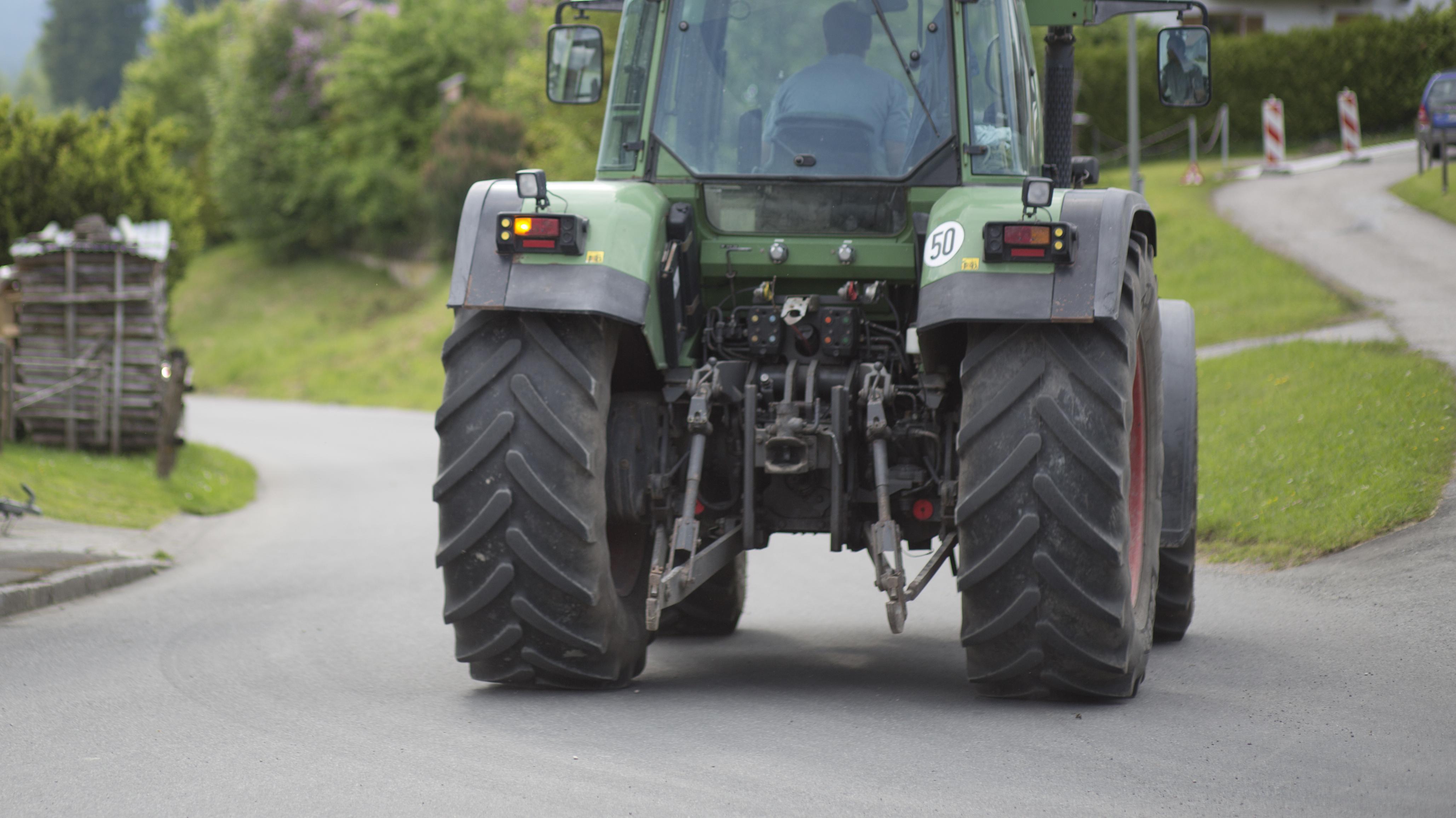Ein Traktor von hinten, der auf einer Straße fährt.