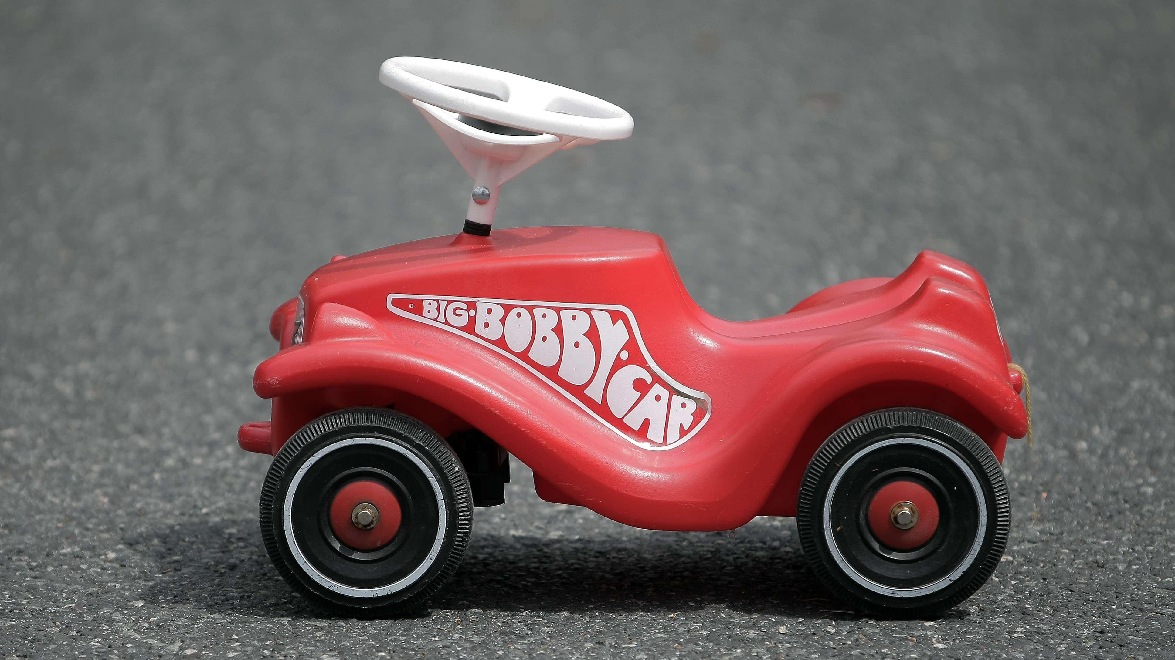 Großaufnahme eines roten Bobby-Cars der auf einer Teerstraße steht
