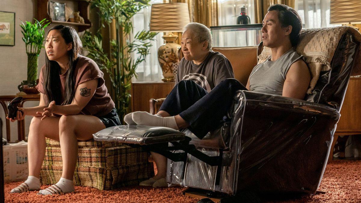"""Awkwafina, eine chinesische US-Amerikanerin, mit älterem und jüngerem Chinesen vor dem Fernseher: Szene aus: """"Awkwafina is Nora from Queens"""""""