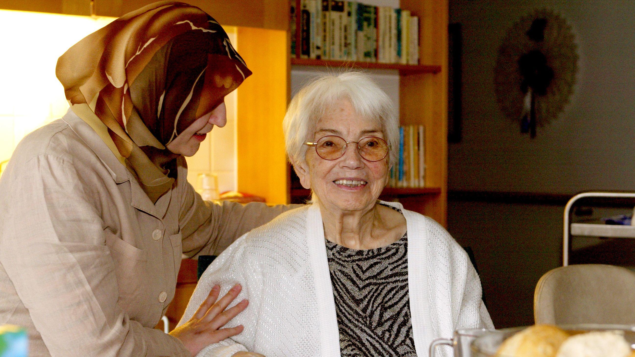 Eine Frau mit Kopftuch legt den Arm um eine ältere, sitzende Frau in einem Altenheim.