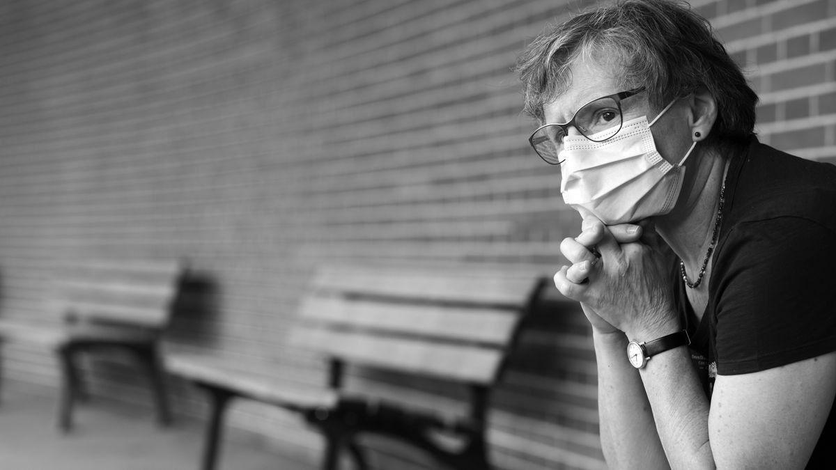 Frau mit Mundschutzmaske sitzt nachdenklich auf einer Bank während der Corona-Krise.