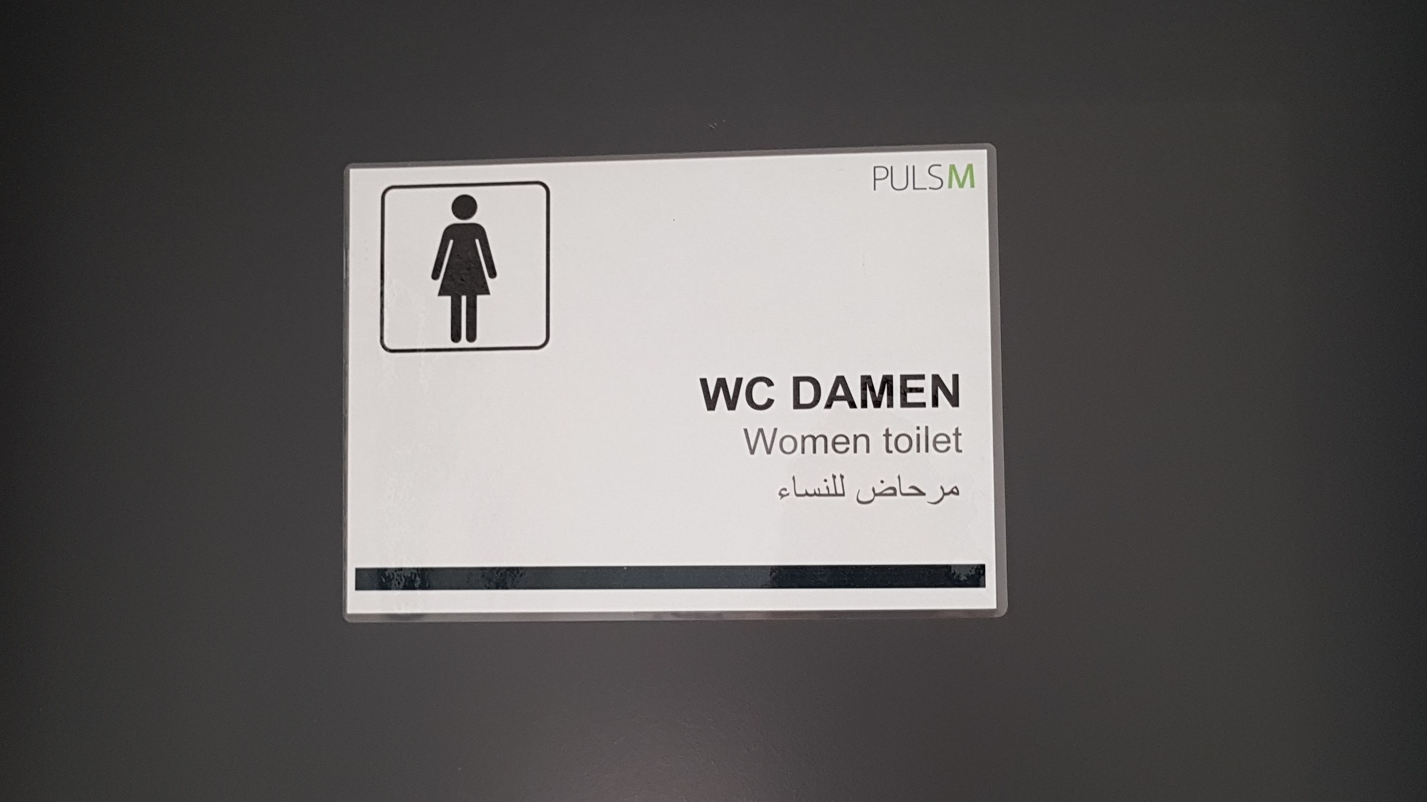 """Ein Toilettenschild mit der Aufschrift """"WC Damen"""", auch auf Englisch und Arabisch."""