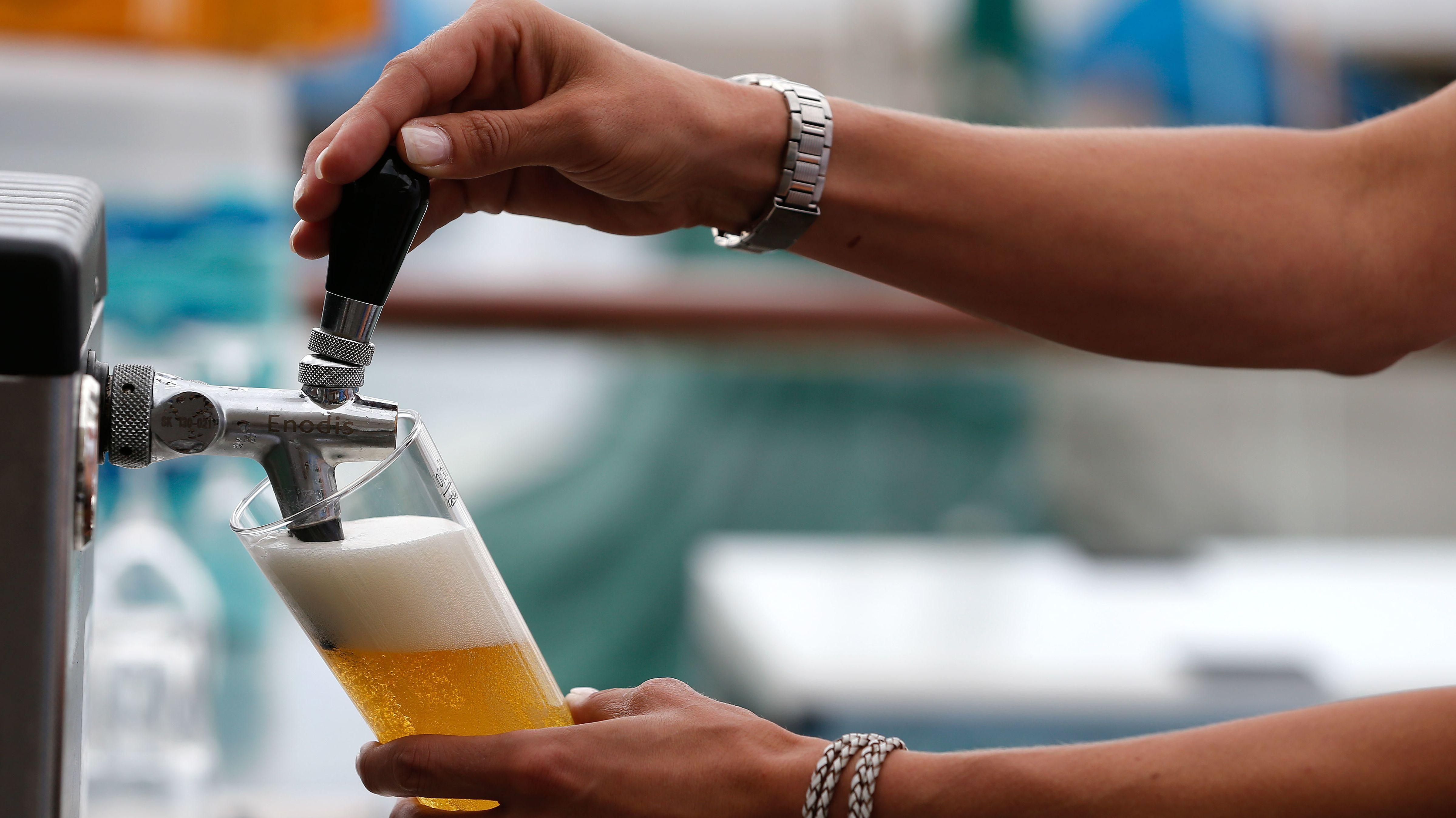 Ein Bierglas wird an einem Zapfhahn befüllt.