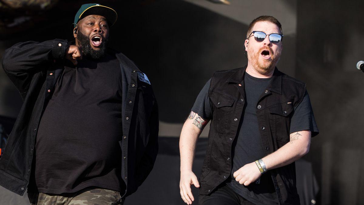 Zwei Männer in schwarzer Kleidung bei einem Auftritt auf der Bühne.