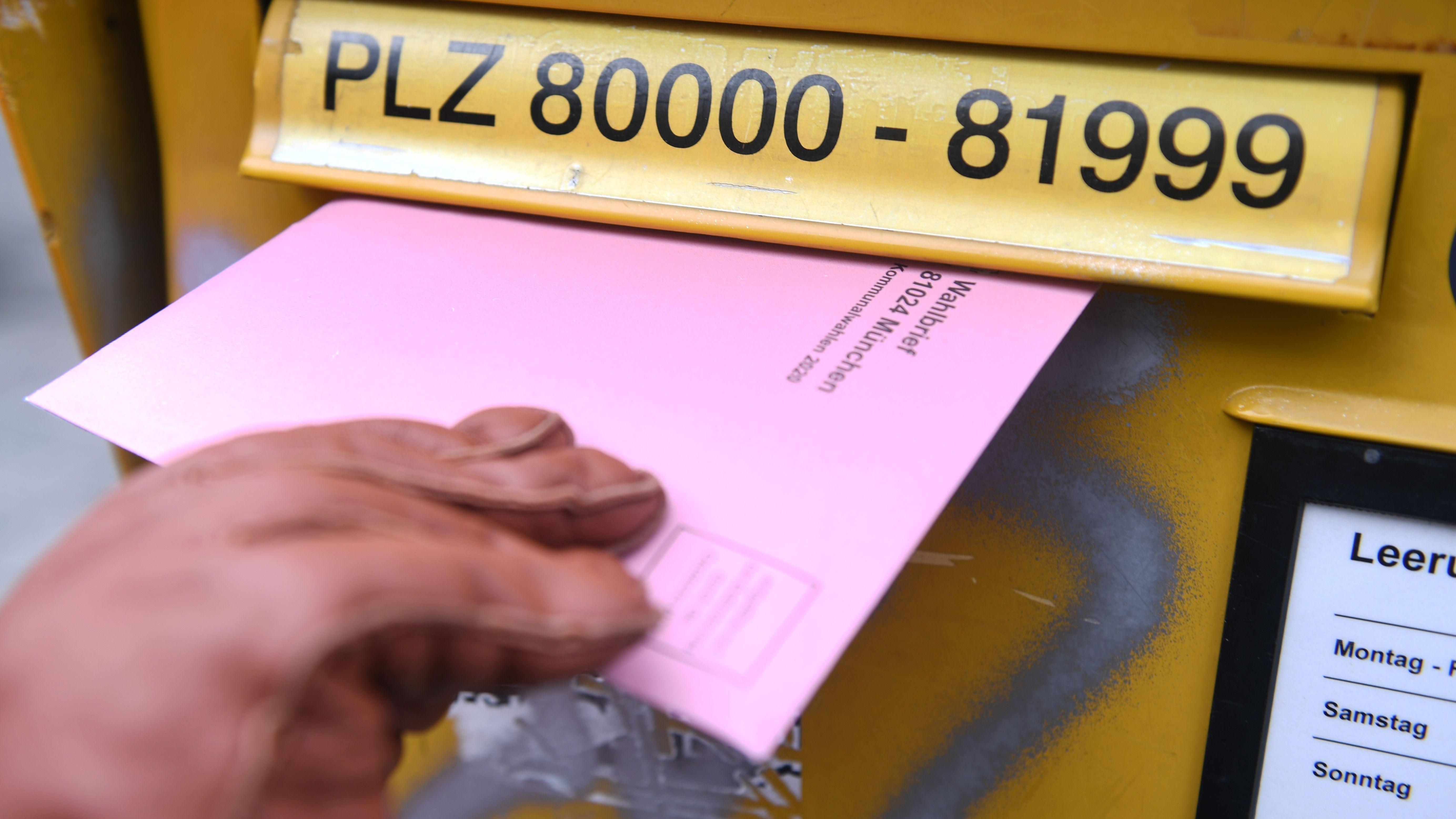 Briefwahlunterlagen werden in  einen Briefkasten eingeworfen