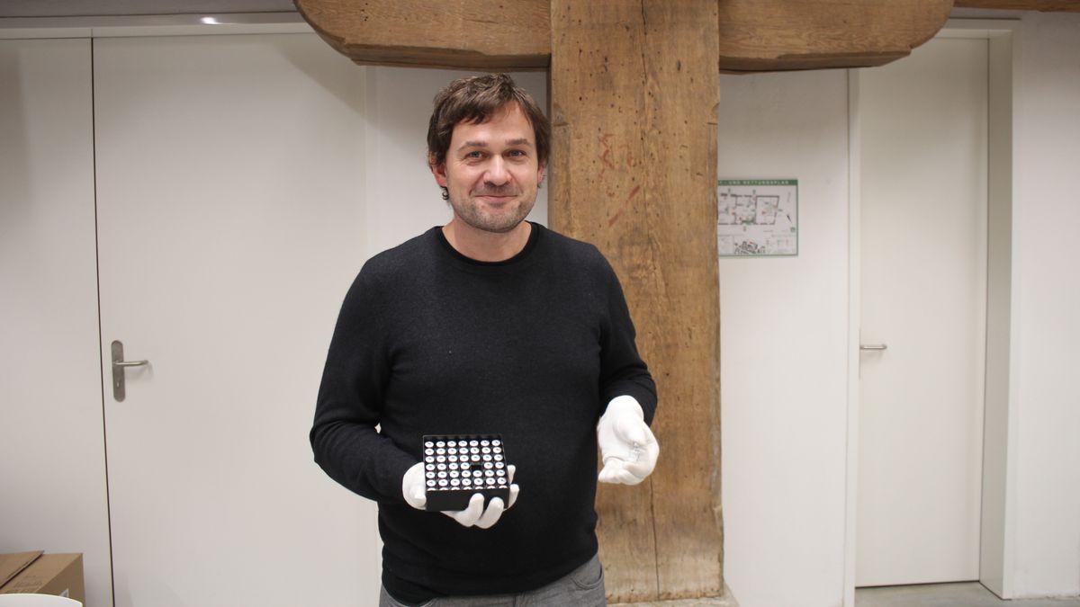Ein Mann steht vor einem tragenden Holzbalken, in der Hand eine schwarze Schachtel.