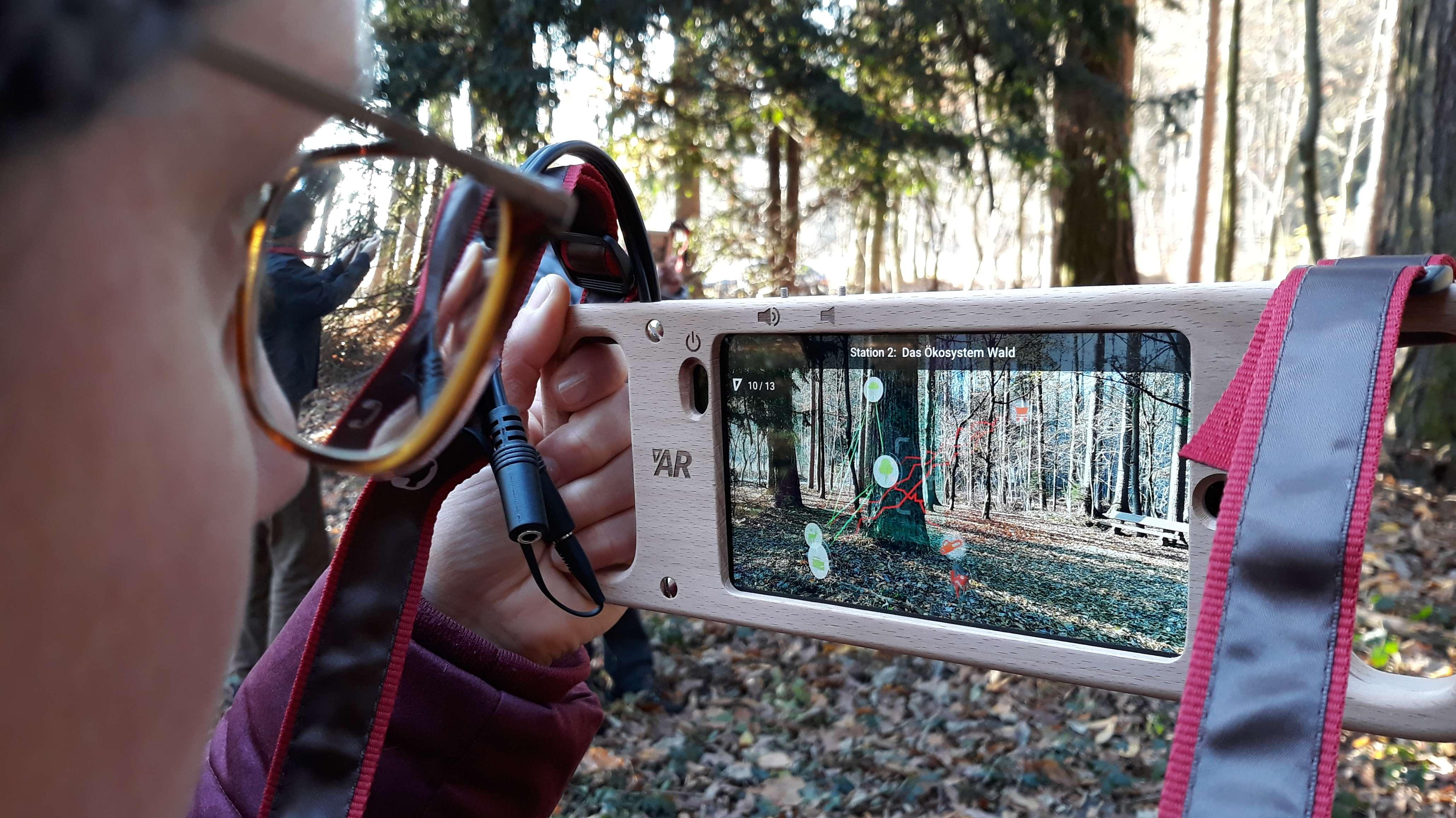 Ein Besucher nutzt die Augmented Reality-Technimk auf dem Waldlehrpfad