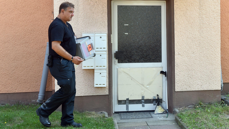 Herne: Schlangenexperte Roland Byner geht mit einer Kiste zu dem Eingang eines Mehrfamilienhaus, um dort nach einer entwischten Kobra zu suchen.