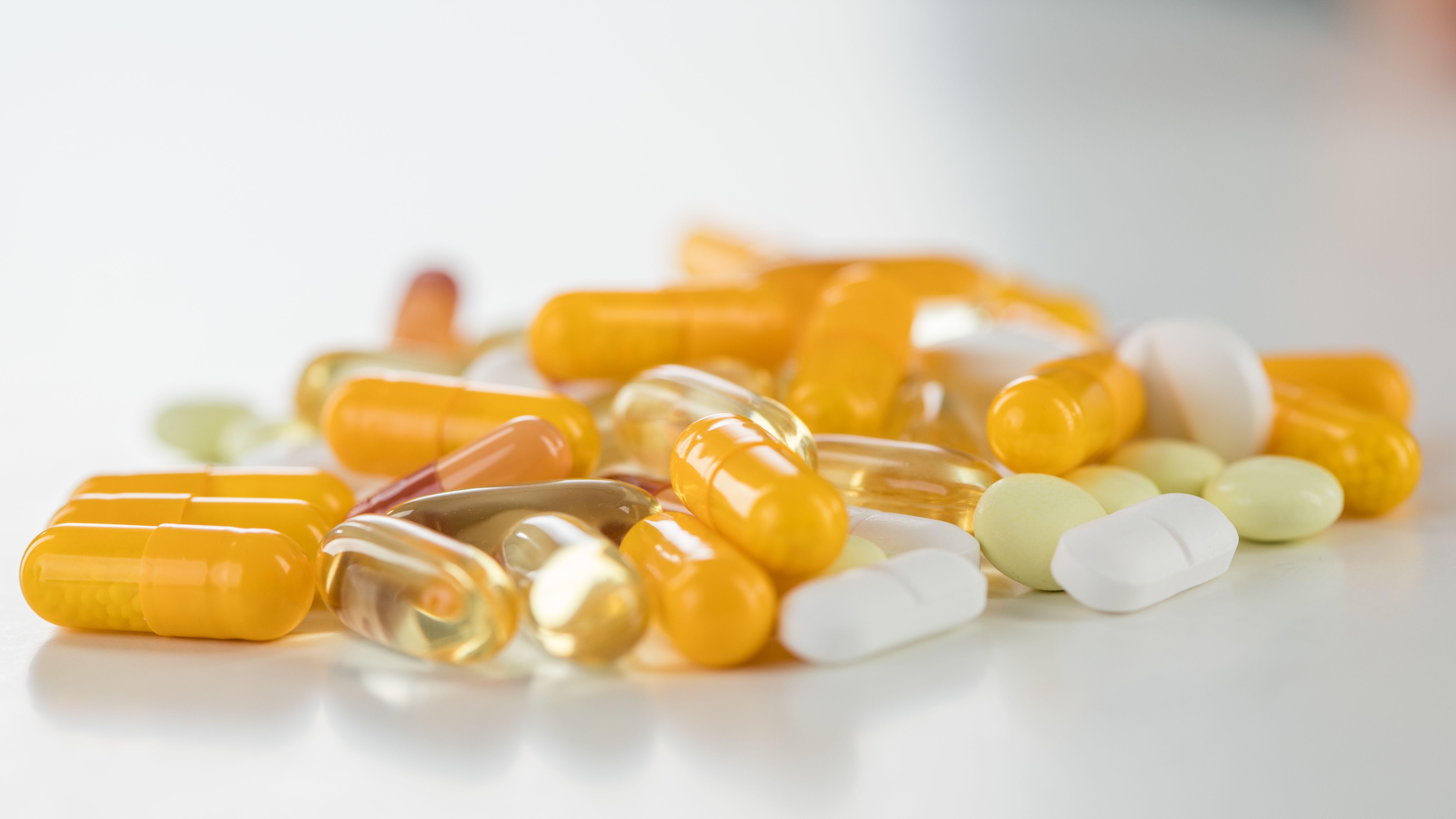 Gelbe, weiße und drichsichtige Tabletten liegen auf einem Haufen
