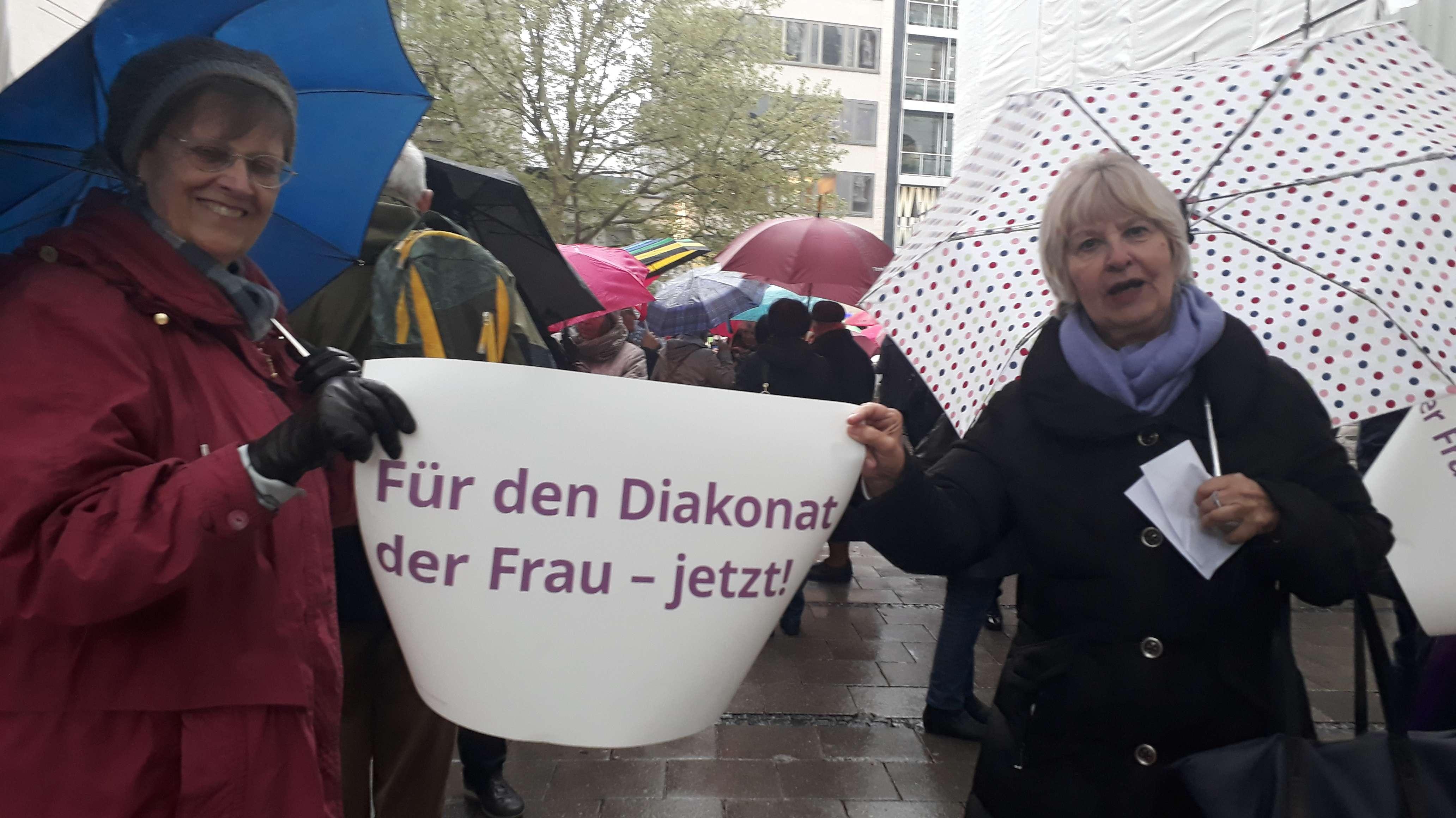 """Zwei Frauen halten ein Plakat mit der Aufschrift """"Für den Diakonat der Frau - jetzt!"""