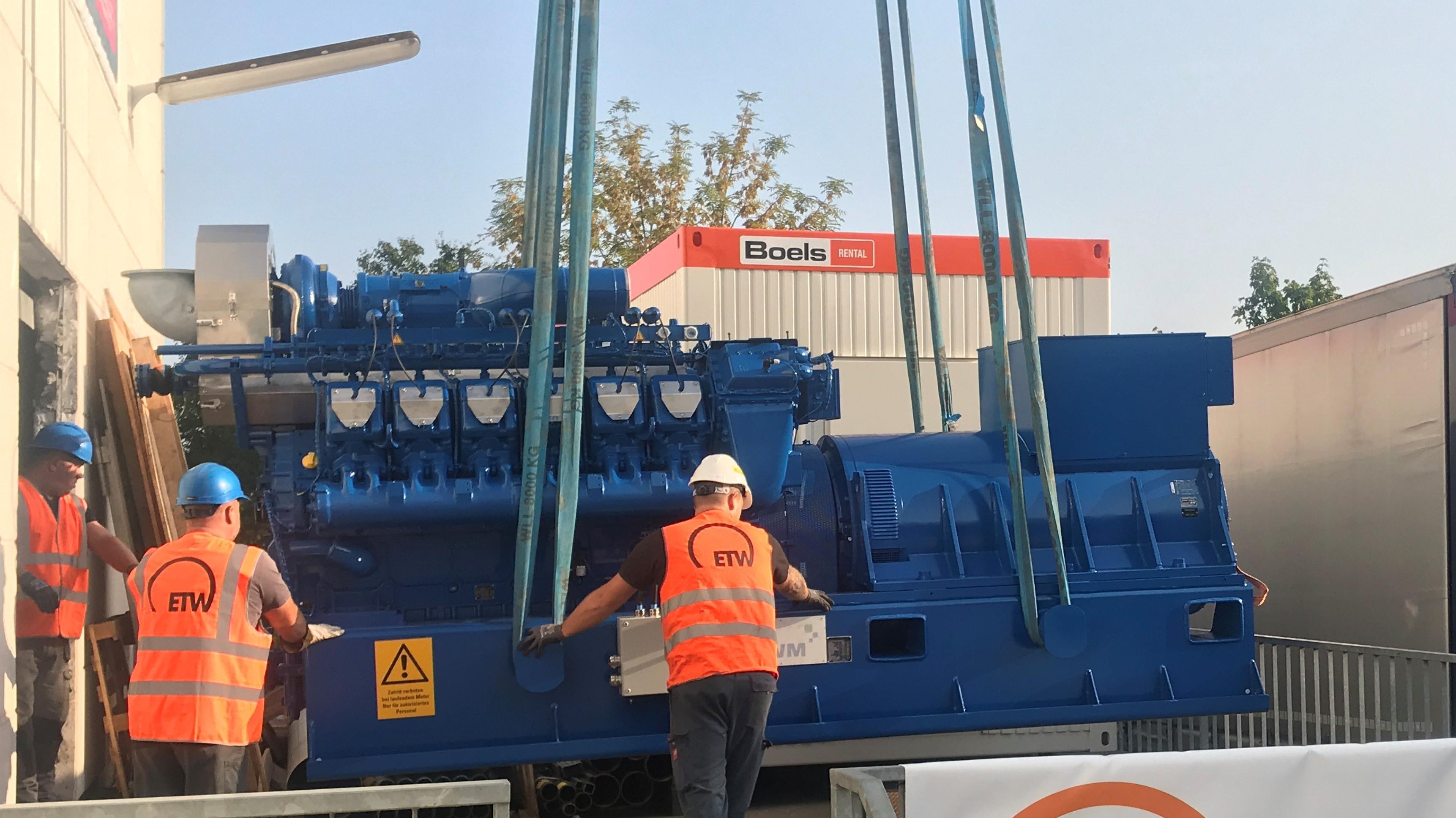 Die erste Gasmotorenanlage wird in das Blockheizkraftwerk gehoben.