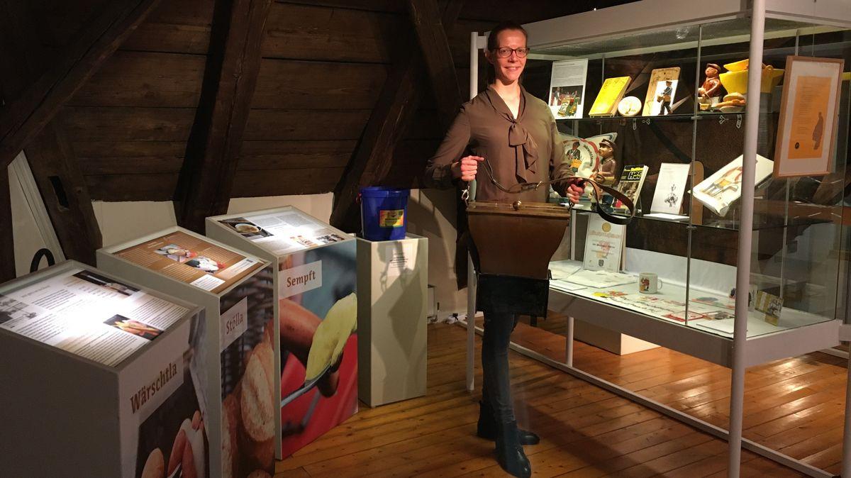 """Museumsleiterin Magdalena Bayreuther steht vor einer Vitrine in der Ausstellung zum Hofer """"Wärschlamo"""" und hält einen Kupferkessel in ihren Händen."""