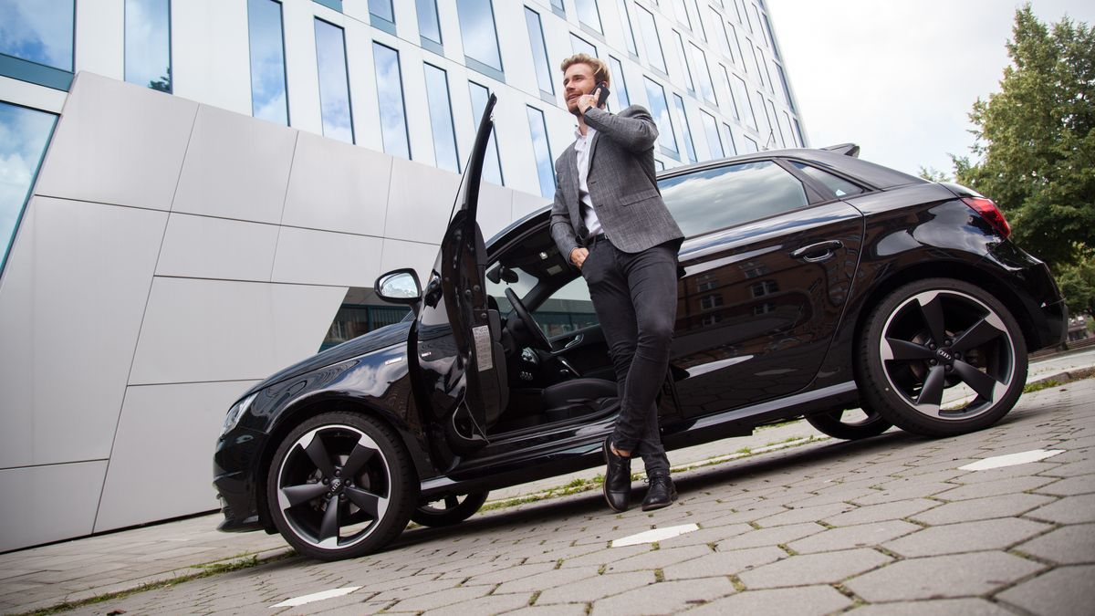 Ein Mann telefoniert vor einem Auto (Symbolbild)