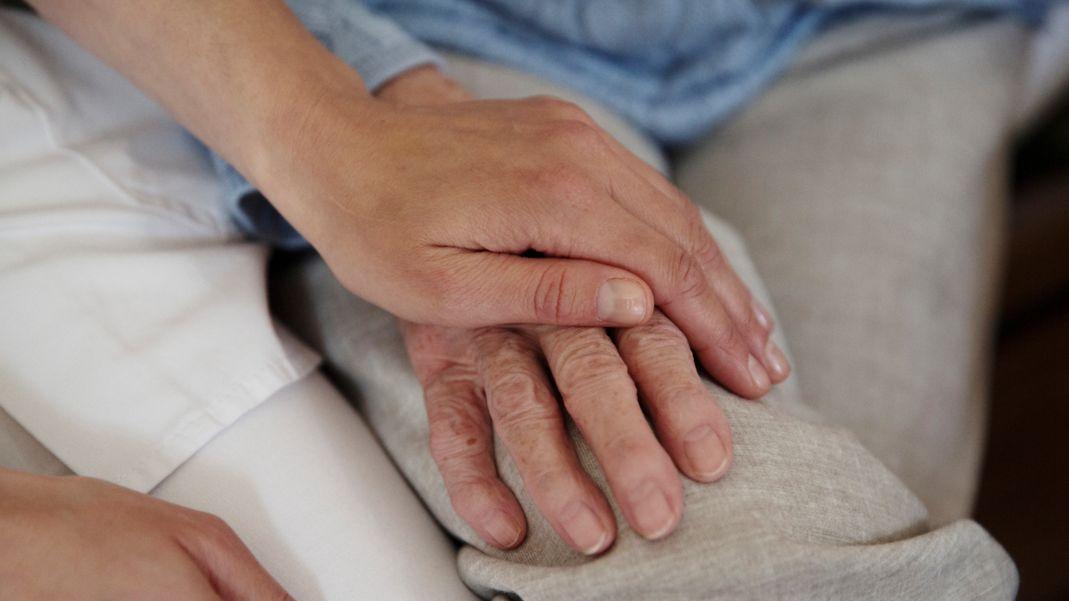 Pfleger hält die Hand eines alten Menschen (Symbolbild)
