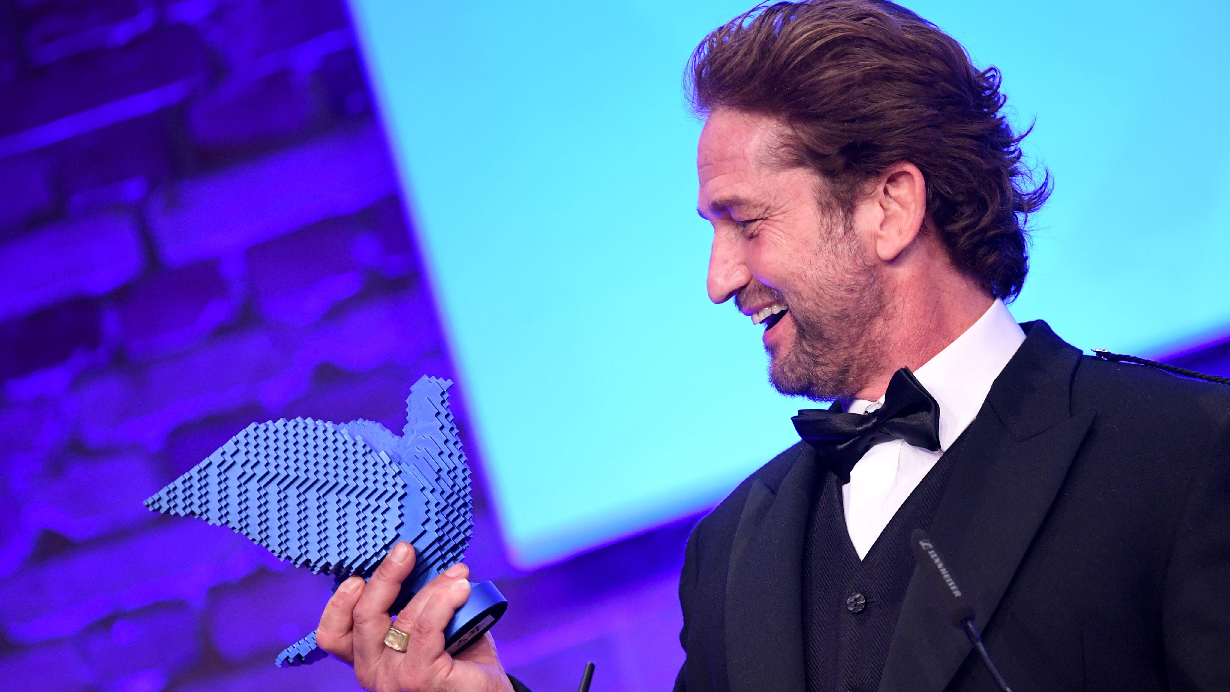 """Gerard Butler bei der """"Cinema for Peace""""-Gala in Berlin: Schauspieler blickt auf Taubenfigur und lacht"""