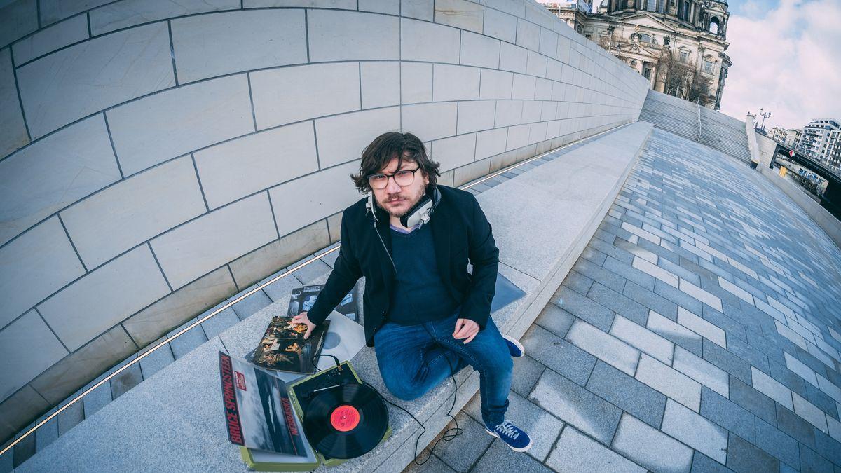 Daniel Decker sitzt mit einer Plattensammlung am Straßenrand.