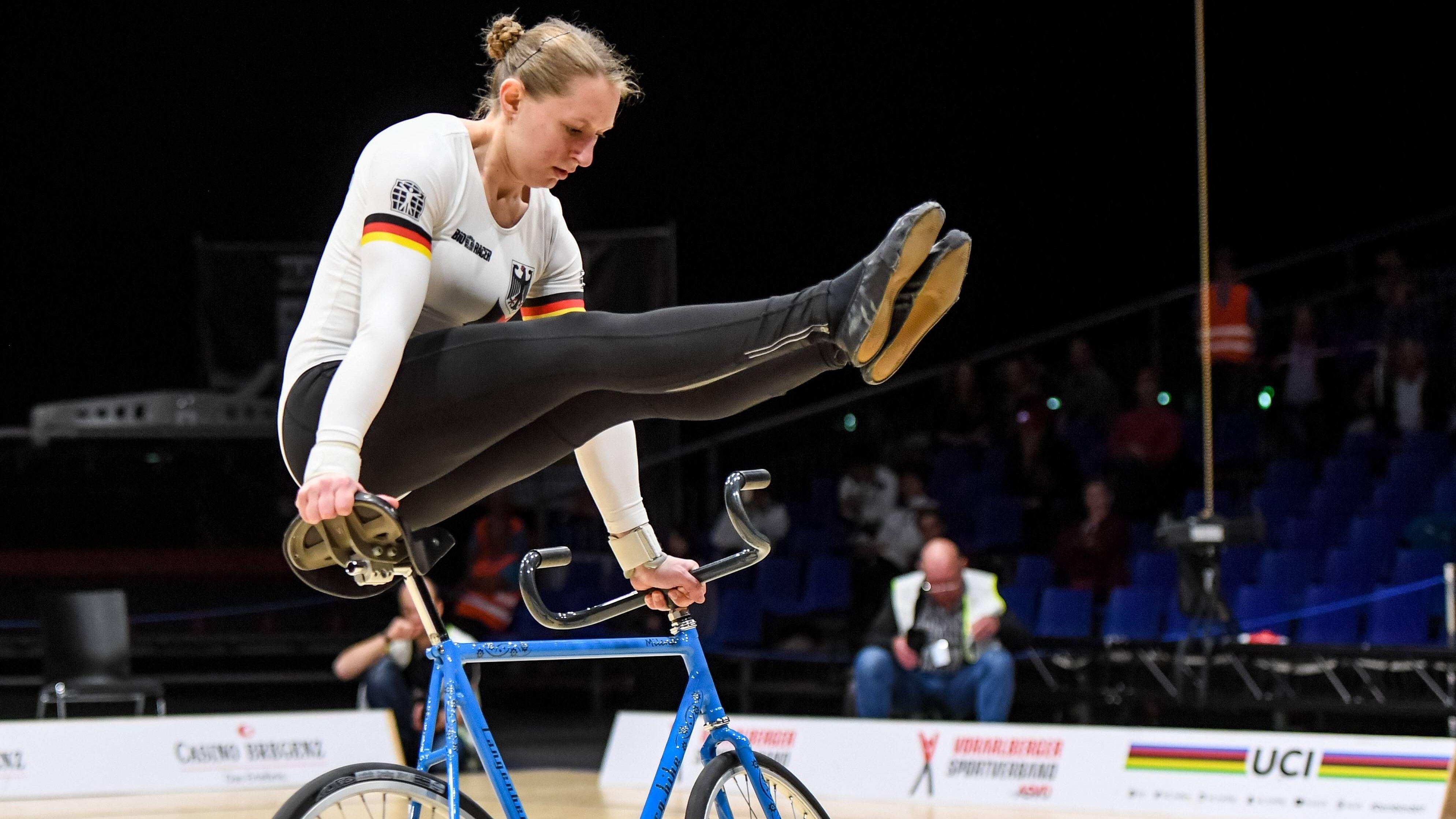 Milena Slupina im Stütz auf ihrem Rad, die Beine vorgestreckt