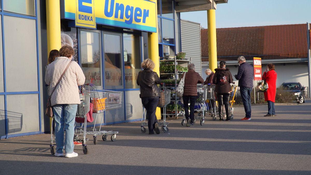 Eine Menschenschlange vor dem Eingang zu einem Supermarkt
