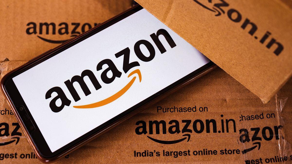 Ein Smarthphone zeigt das Amazon-Logo und liegt dabei zwischen Kartons mit der Beschriftung amazon.in