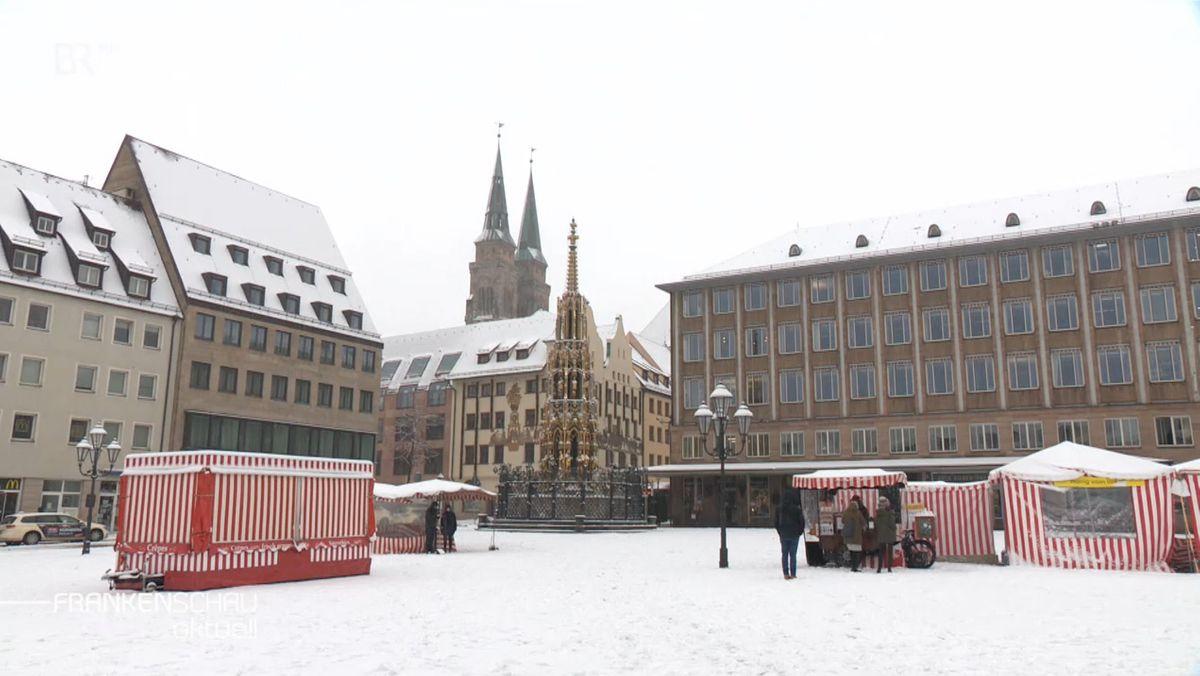 Ein schneebedeckter Platz mit rot-weißen Buden, davor stehen Leute, dahinter Gebäude und eine Kirche.