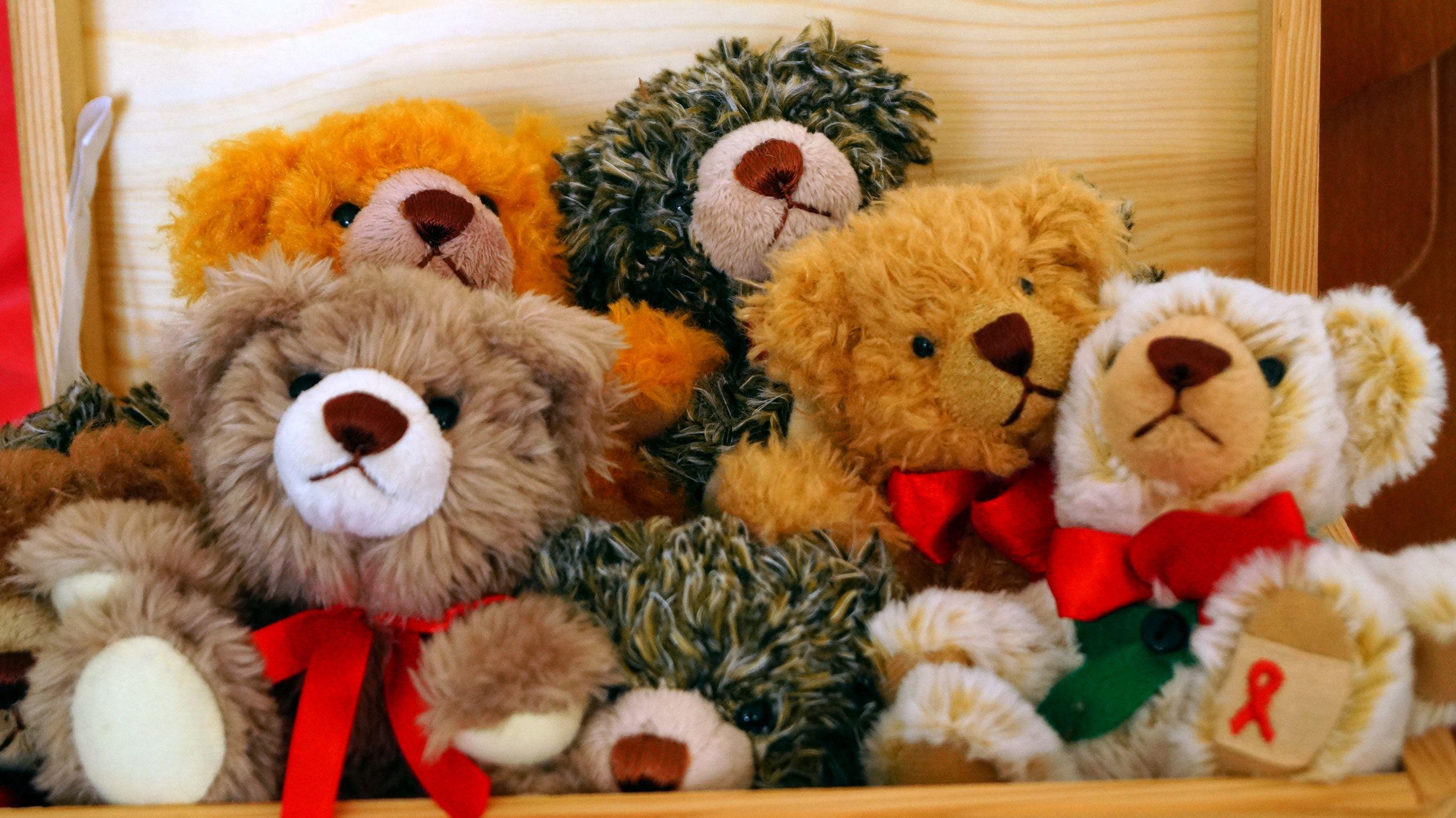 Teddy-Bären mit roter HIV-Schleife helfen, Spenden für Menschen mit HIV zu sammeln