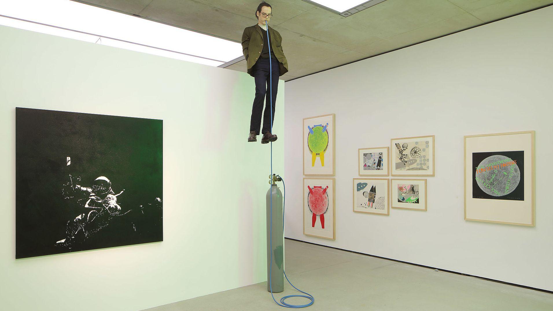 """Teile der Ausstellung """"Fly me to the Moon"""". Im Zentrum: Eine an der Decke schwebende Figur mit einem Heliumschlauch im Mund"""