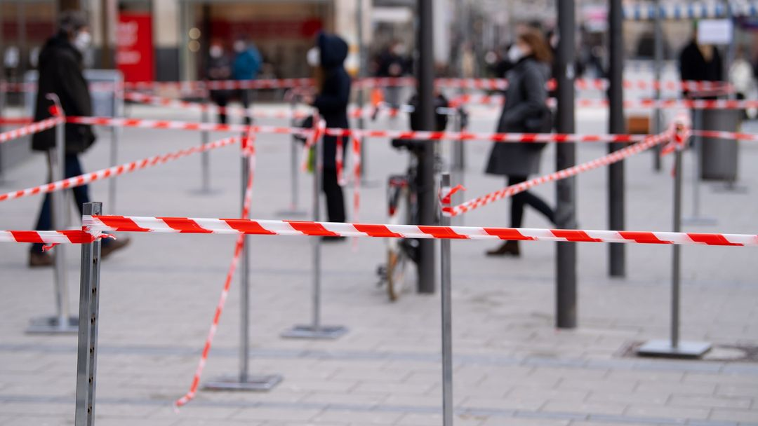 Bayern, München: Einkäufer warten vor einem Geschäft in der Innenstadt in einer Warteschlange.