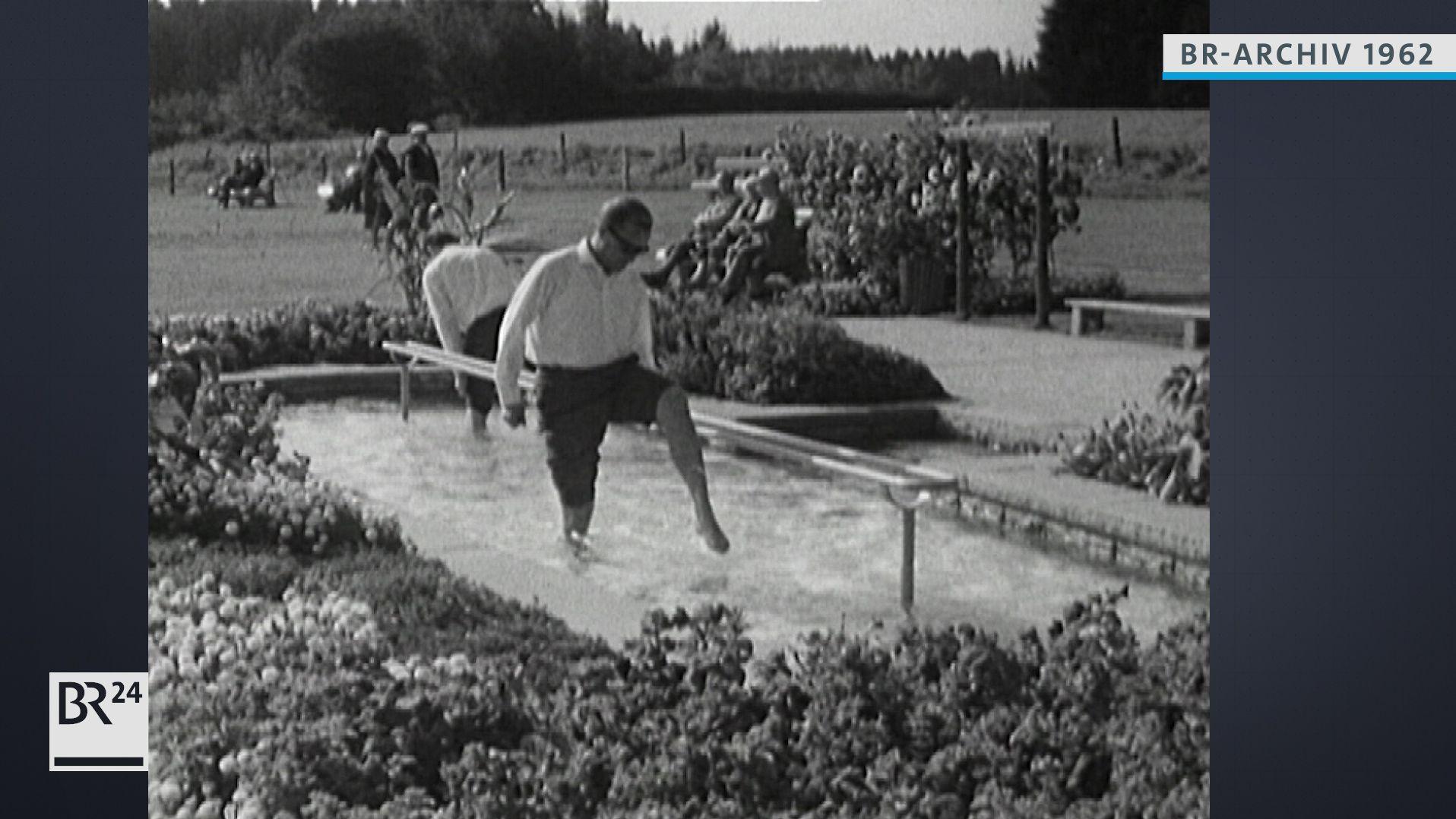 Zwei Männer beim Wassertreten im Kneippbecken im Freien
