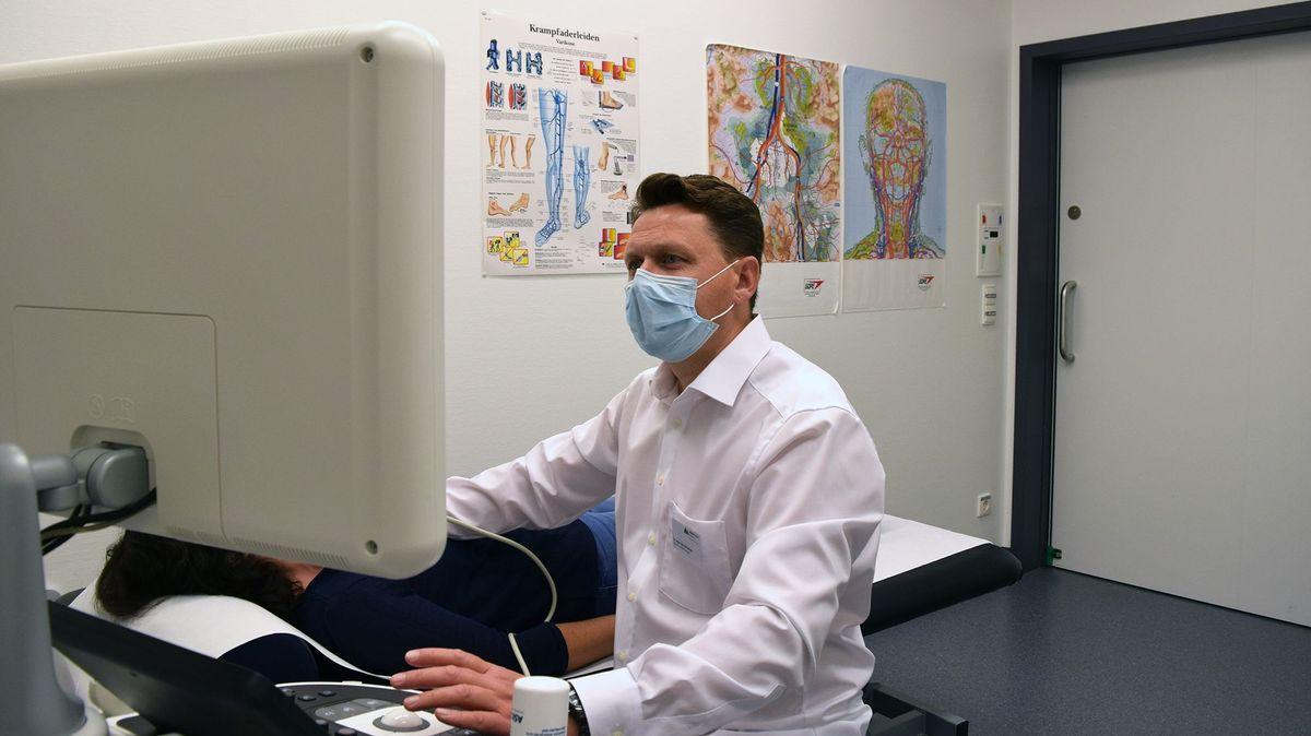 Ein Arzt beim Ultraschall der Halsschlagader